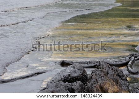 crude oil spill on the beach - stock photo