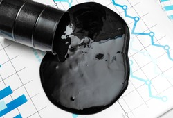 Crude oil spilled from container on financial graphs. Business concept. Top view.