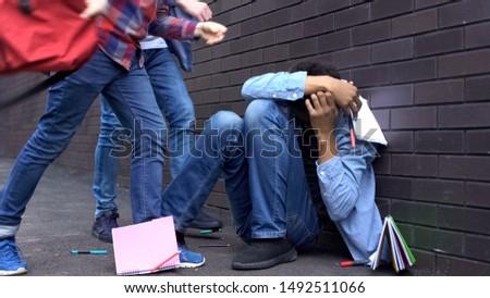 Cruel teenagers scattering classbooks of afro-american boy, school bullying Сток-фото ©