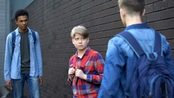 Cruel teenagers threatening younger boy, physical intimidation, school bullying