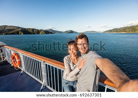 Cruise couple tourists taking selfie on New Zealand travel. People traveling on ferry boat Marlborough sounds taking self-portrait picture with mobile phone smiling at camera.