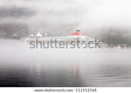cruise ferry moored in the fjord during dense fog somewhere in Norway