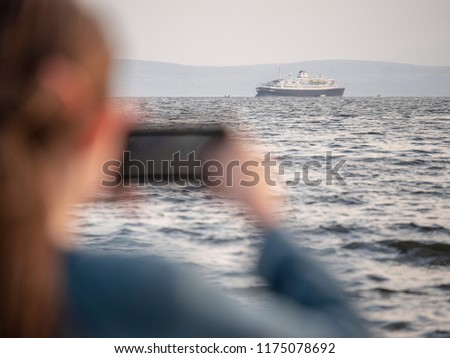 Cruise liner in the ocean, girl taking picture on her phone,  Cruise ship is in focus, the girl is out of focus.
