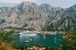 Cruise liner moored at the walls of the old town of Kotor, near a rocky mountain.