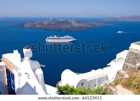 cruise liner motoring into the caldera below the cliffs of the capital city of fira on the greek island of santorini