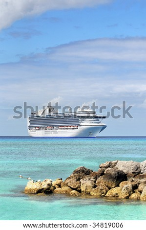 Cruise ship anchored in tropical waters with rocks in foreground