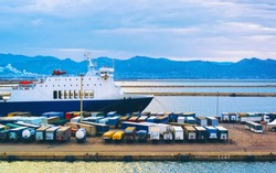 Cruise ship and containers in Mediterranean Sea at port at Cagliari, Sardinia island, Italy summer. Truck trailer. Wagons of vans. Mixed media.