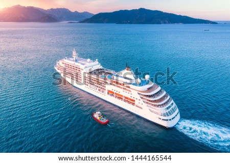 Cruise ship at harbor. Aerial view of beautiful large white ship at sunset. Colorful landscape with boats in marina bay, blue sea, sky. Top view from drone of yacht. Luxury cruise. Floating liner