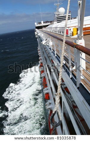 Cruise ship at high speeds on the open sea headed for a beautiful travel destination.