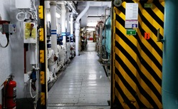 Cruise ship engine room interior with water tight doors electrical and diesel engines, water pipes, measuring instruments