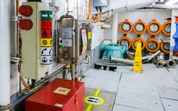 Cruise ship engine room interior with water tight doors electrical and diesel engines, water pipes, measuring instruments, warning signs