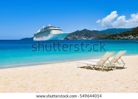 Cruise ship in Caribbean Sea with beach chairs on white sandy beach.\nSummer travel concept.