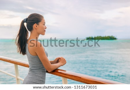 Cruise ship luxury Tahiti vacation island hopping French Polynesia Oceania world tour in yacht on tropical ocean travel - Young tourist Asian woman watching sunset on deck of cruising boat.