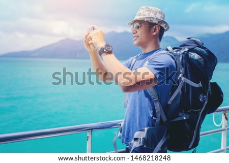 Cruise ship man with backpack using mobile phone on travel vacation at ocean. Handsome man using smartphone take a seascape photo while travel on cruise ship