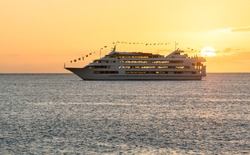 Cruise ship or ferry boat sailing towards setting sun off coast of Waikiki Oahu Hawaii
