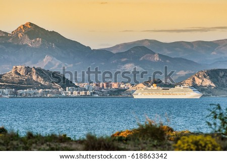 Cruise ship sailing at Mediterranean sea with Alicante and mountains background