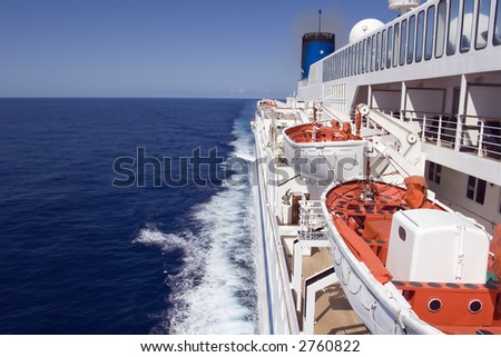 Cruise ship underway on the smooth ocean, showing lifeboats.