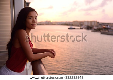 Cruise ship vacation woman enjoying balcony at sea with beautiful sunset on travel at sea. Relaxed woman enjoying private balcony in stateroom. Asian Chinese / Caucasian woman in dress on cruise liner