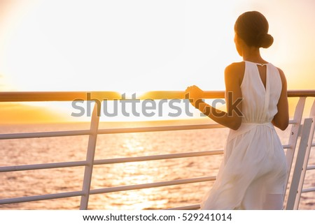 Cruise ship vacation woman enjoying sunset on travel at sea. Elegant happy woman in white dress looking at ocean relaxing on luxury cruise liner boat.
