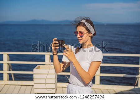 Cruise ship woman using mobile phone on travel vacation at ocean. Girl texting sms on tropical holidays. Internet on international seas concept. Tourist looking at her holiday pictures