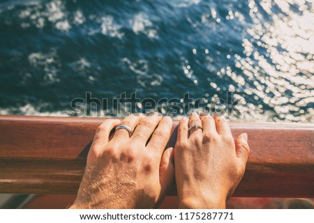 Cruise travel honeymoon married couple. Newlyweds woman and man with wedding bands rings on ship deck.