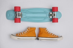 Cruiser board and gumshoes on white background. Youth concept. Top view