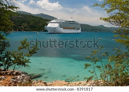 Cruiseship anchoring in a caribbean bay - stock photo