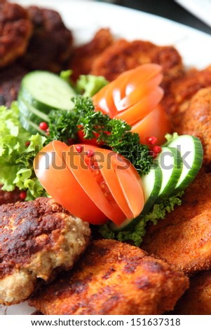 Crumbed fried meat and fish on a buffet table at a catered event with fresh salad ingredients as a garnish