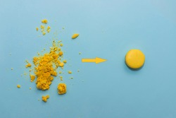 Crumbled yellow macaroon cookie arrow points to unbroken macaroon on blue flat background. The concept of transformation broken to unbroken