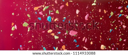 Crumbs of a multicolored chalk, crayon fly on a vinous background. Joy, Carnival. Flying. Panorama. Game for children #1114933088