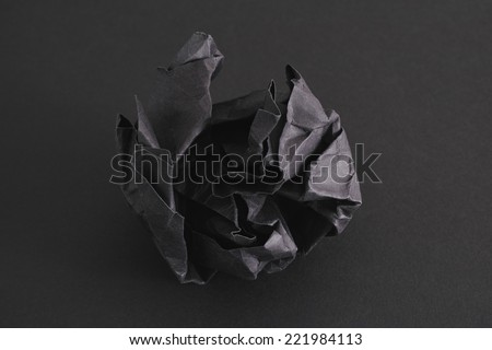 Crumpled black paper ball on a black background.