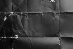Crumpled black paper with wrinkles and rubbed corners. Old wrapping dusty cardboard. Abstract dramatic background. For design and titles.