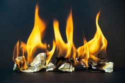 Crumpled dollar bills burning fire on a dark background. Economic crisis and downturn and bankruptcy, shutdown.
