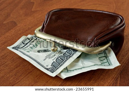 """Crumpled 100 dollar bills in leather change purse depicting """"small change"""".  Conceptual image for inflation."""