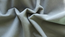 crumpled folds of gray material with a short textured pile, curved surface of dense soft fabric of an ash shade, smooth curves and shaded lines of neutral fabric drapery, plain textured background