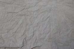 Crumpled linen fabric texture of coarse gray fabric, burlap background in close up, weave threads, fabric after washing, un-ironed canvas