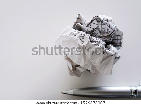 Crumpled paper and a silver pen on white blank background with copy space - concept of first time writing / writers block , or lack of inspiration to get a better idea