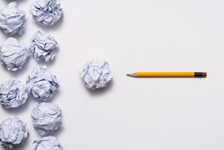 Crumpled paper ball and pencil on the white background