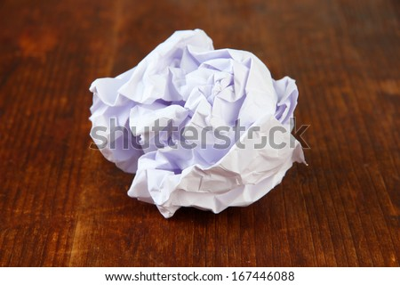 Crumpled paper ball on wooden background
