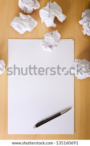 Crumpled paper balls and blank sheet of paper with pen