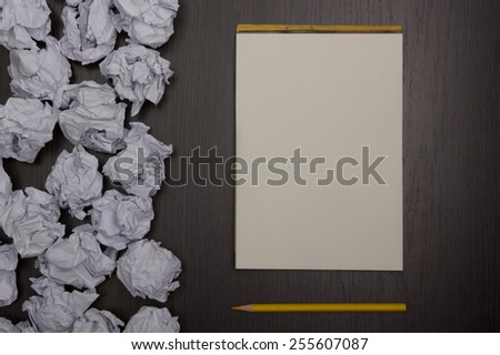 Crumpled paper balls and blank sheet of paper with pencil on black background. Paper wad. Creativity problems. Searching ideas.