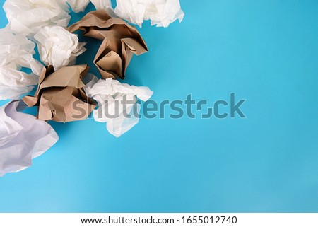 Crumpled paper balls brainstorming not idea on blue background.