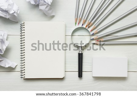 crumpled paper balls, magnifying glass, pencils and notebook with blank white sheet  on wooden table. Creativity crisis concept #367841798
