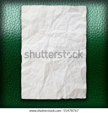 Crumpled paper on green leatherette background