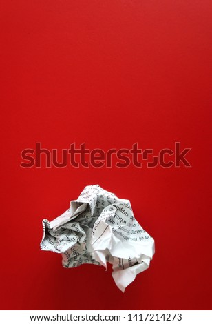 Crumpled paper on red background with copy space. Concept of first time writing /writers block.