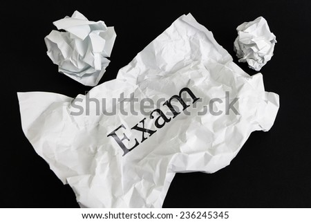 Crumpled paper sheet with word Exam isolated on black #236245345