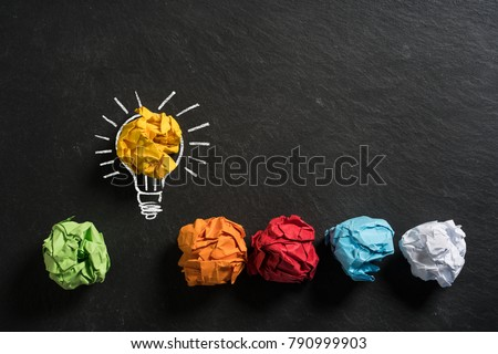 crumpled paper symbolizing different solutions with one standing out on a slate background