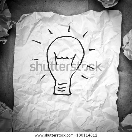 Crumpled paper with a lightbulb idea concept and crumpled paper attempts around it in black and white Zdjęcia stock ©