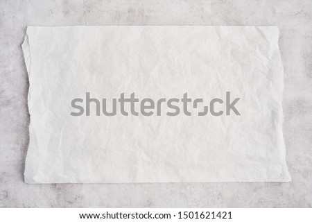 Crumpled piece of white parchment or baking paper on grey concrete background. Top view. Copy space for text and design element.