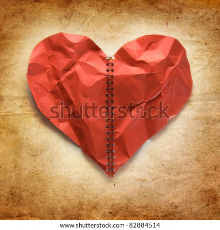 Crumpled red paper heart on vintage background. Concept.